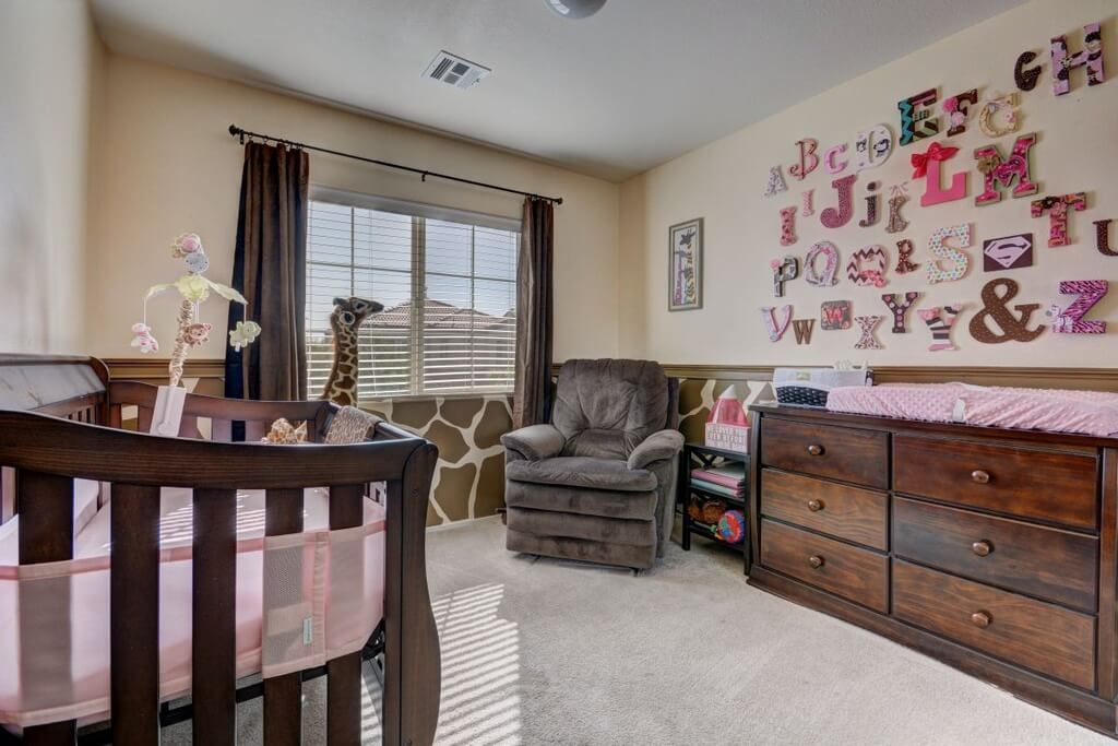 Nursery room with pink letters decorations on the wall and a gray carpet flooring.