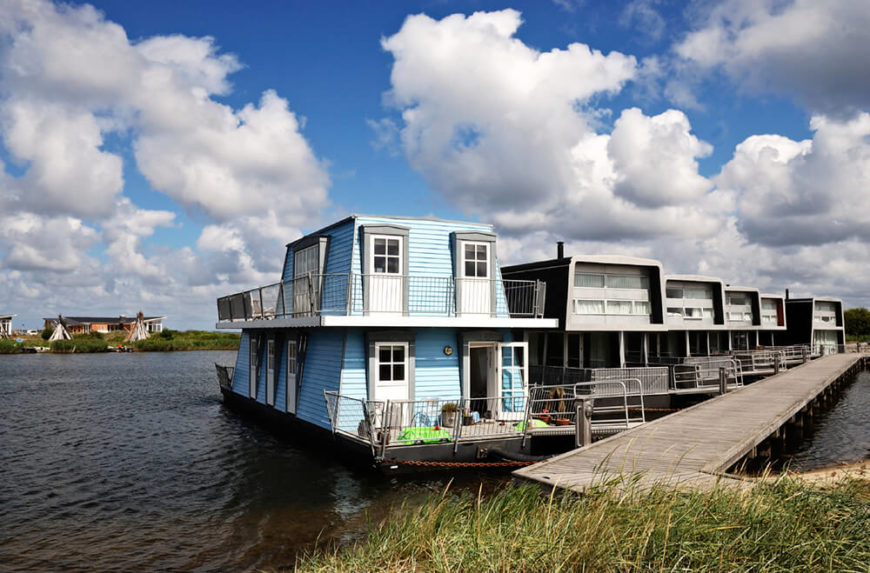 A lovely blue houseboat moored off of a large dock along side many other permanent houseboat homes.