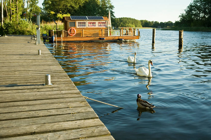 A wooden houseboat moored off of a dock on a private lake, with swans and ducks frequenting the open spaces.