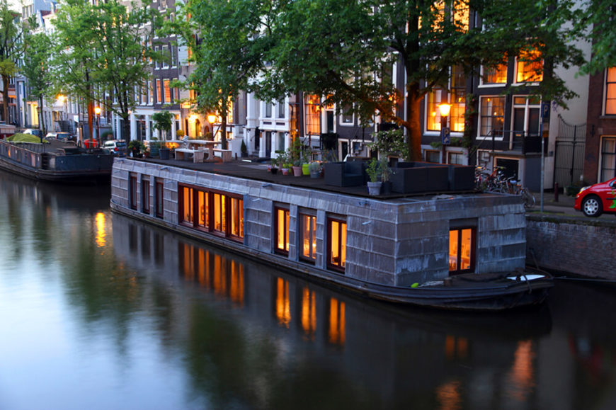 A large shingled houseboat in Amsterdam with a variety of potted plants and patio furniture on the roof.