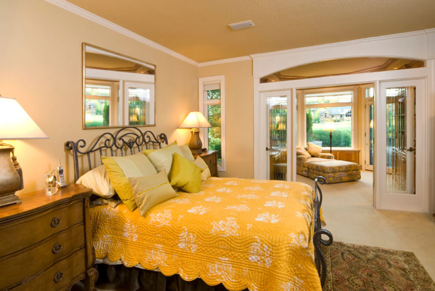 This large master bedroom en suite features a set of glass French doors dividing the more private sleeping quarters from a family-room styled space. That second segment features its own direct patio access.