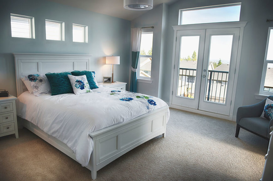 In this upper level bedroom decked out in white and sky blue, an abundance of smaller windows complement the set of white framed French doors, spilling in natural light throughout.