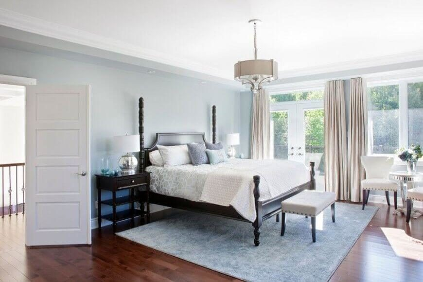 This bright bedroom features high contrast between dark wood flooring and sky blue walls and area rug. White framing wraps full height windows and French doors to the right.