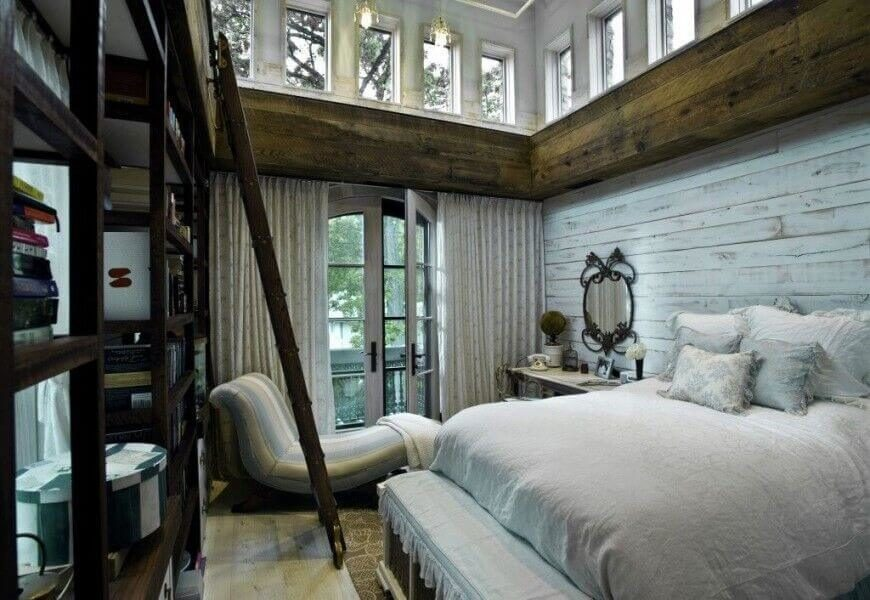 Rich rustic wood informs the look of this cozy but vertically spacious bedroom. A tall set of bookshelves with accompanying ladder hang in front of a set of French doors that provide balcony access.