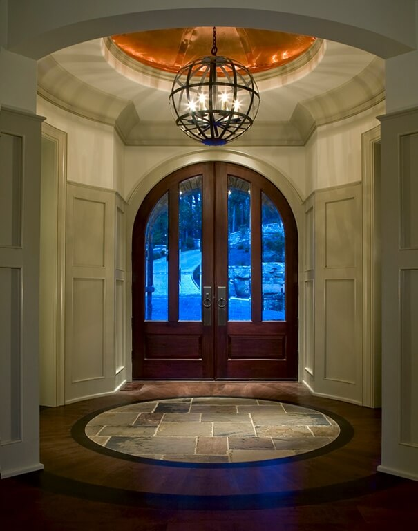 The pale gray three-quarter wall wainscoting in this circular foyer gives the walls a taller appearance and balances the dark floors while matching the stone centerpiece to the room. The arched copper ceiling is a gorgeous touch when viewed with the globe-like chandelier