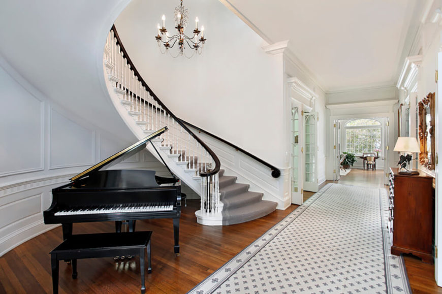 Bright white walls are broken up by the selective use of black, gray, and stunning wood accents. The wainscoting follows the sweep of the stairs, both below and above, gracefully carrying the eye up to the gorgeous chandelier suspended from the ceiling.