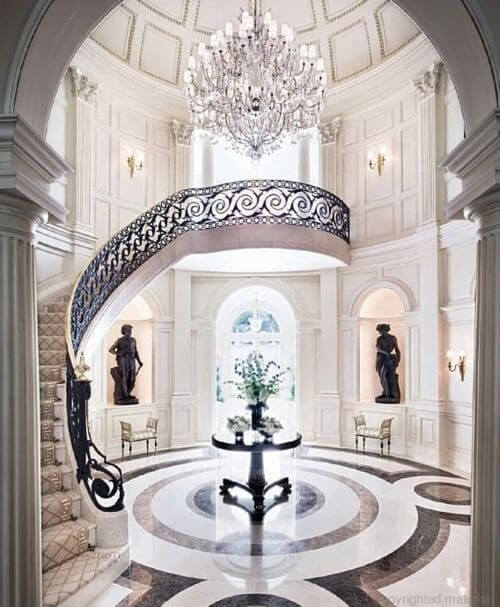 This room exudes luxury from every alcove. The black sculptures are accented by the black furniture, banister, and marble inlaid floor. Subtle off white and gold touches add to the stately feel of the room, as does the huge chandelier. Pillars framing the entrance to the room maintain a classical architecture.