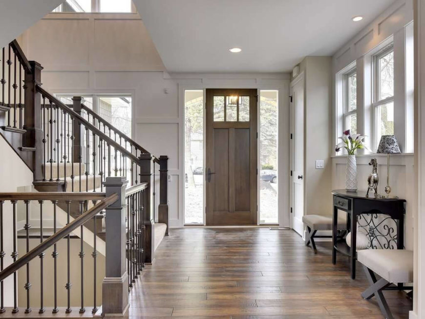 Dark wood used throughout this room is balanced by a used of white, pale colors, and light. The straight, structured lines of the stairs cutting into the space at different angles adds plenty of visual interest to open space - carrying the eye both up and down into the space.