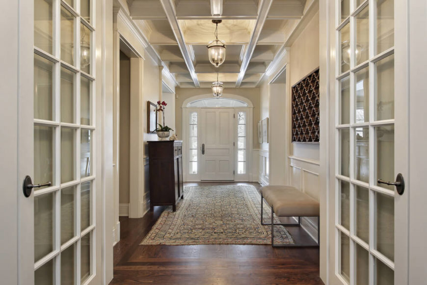 The coffered ceiling in this entryway creates extra interest that is mimicked in the dark wood wall art. The pale walls and white wainscoting balances the dark wood floor and brightens up the enclosed space, which lacks any large windows. The pale but richly patterned rug also helps to balance the colors in the room.