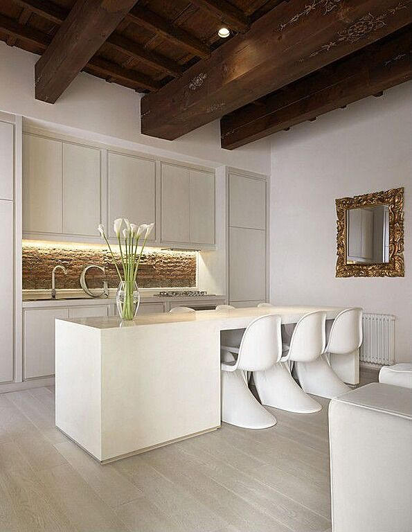 White and pale gray create this space, broken up only by accents of gold and green; until you get to the dark, exposed beams on the ceiling of the room. The kitchen itself flourishes with the addition of the rough stone backsplash bringing in color, though neutral, that stands out against the light hues of the rest of the room.