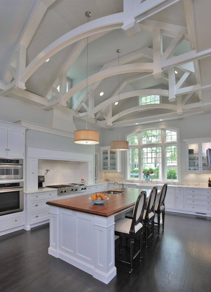 Soaring ceilings are broken up by beautiful arching beams in this stunning white kitchen. Dark floors counter the lightness of the room with the help of the barstools. A gorgeous wood countertop breaks up the space and adds another level of color to the room.