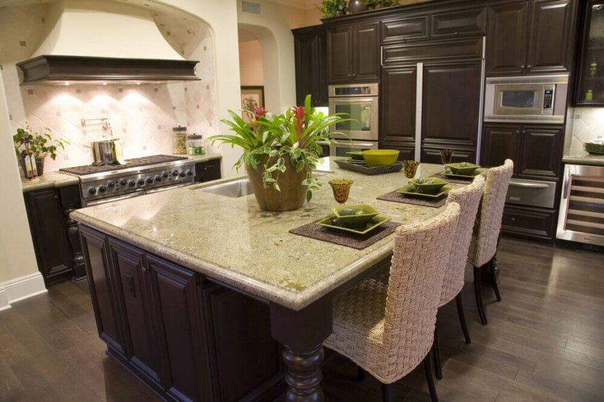 Dark brown cabinets are offset by a slightly paler brown floor while the off-white tile backsplash is complemented by the rough woven chairs standing attention at the island. Bright green accents are used around the room to bring in a pop of color to the otherwise dark space.