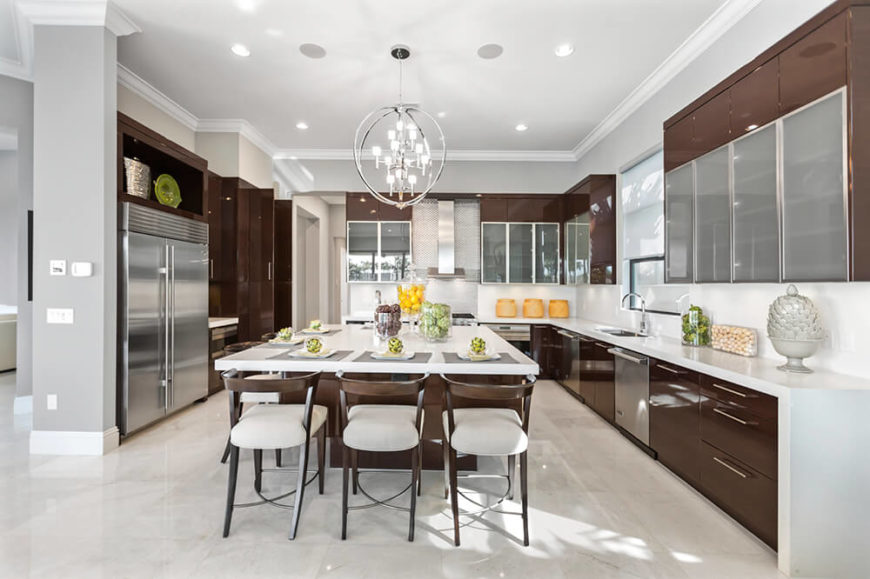 Chocolate brown and bright white strike an easy balance in this room with sleek silver hardware accents. The high-gloss sheen of the room makes sure to reflect plenty of light around the room and pops of bright colors liven up the kitchen design.