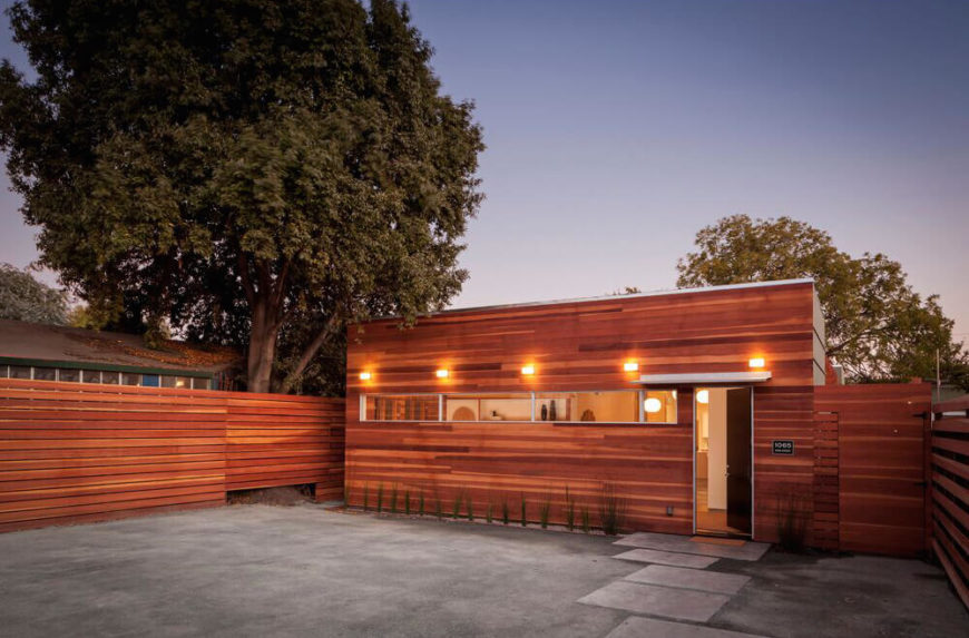 Here we see the front entry, a more private facade than the back of the home, with a slim row of windows allowing a narrow glimpse inside. The rich natural wood surrounds this space, informing the rest of the structure.