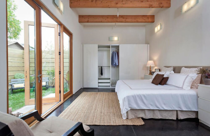 The master bedroom is awash in white, contrasting with the dark flooring that appears throughout the home. In here we see more of the exposed wood beams, as well as a large set of wood framed glass French doors with direct access to the backyard.