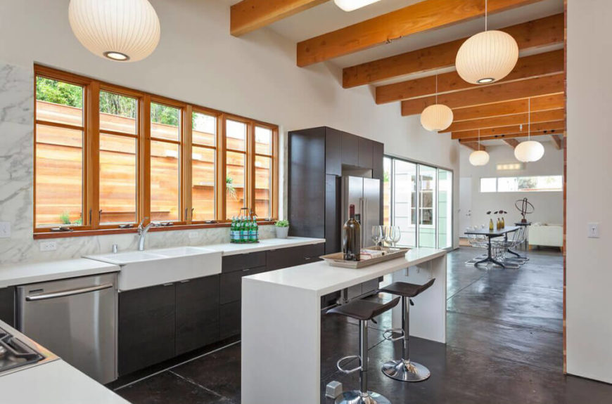 Turning toward the rest of the massive open space, we can see that the island hosts a pair of modern bar stools for in-kitchen dining, while a large row of windows pours in natural light. The rich wood ceiling beams run the length of the home, connecting the disparate ends.