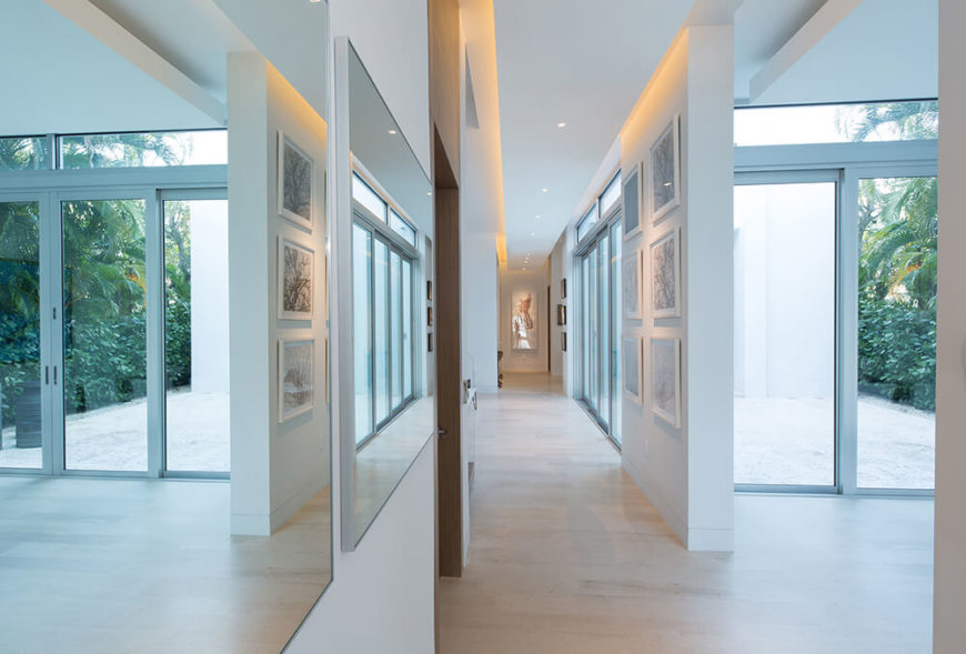 Upon entering the home, one wall is lined with mirrors, making the narrow hallway feel absolutely enormous, as though you were walking into an open-concept home. Looking down the hallway we can see more sliding glass doors and a hallway lined with art in subtle colors.