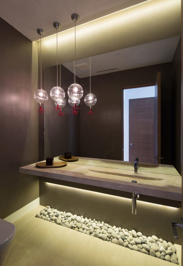 The main floor bathroom consists of a floating stone countertop with an integrated basin and a cluster of glass orb pendant lights with red coral-like ends. A drainage basin filled with round stones sits below the sink.