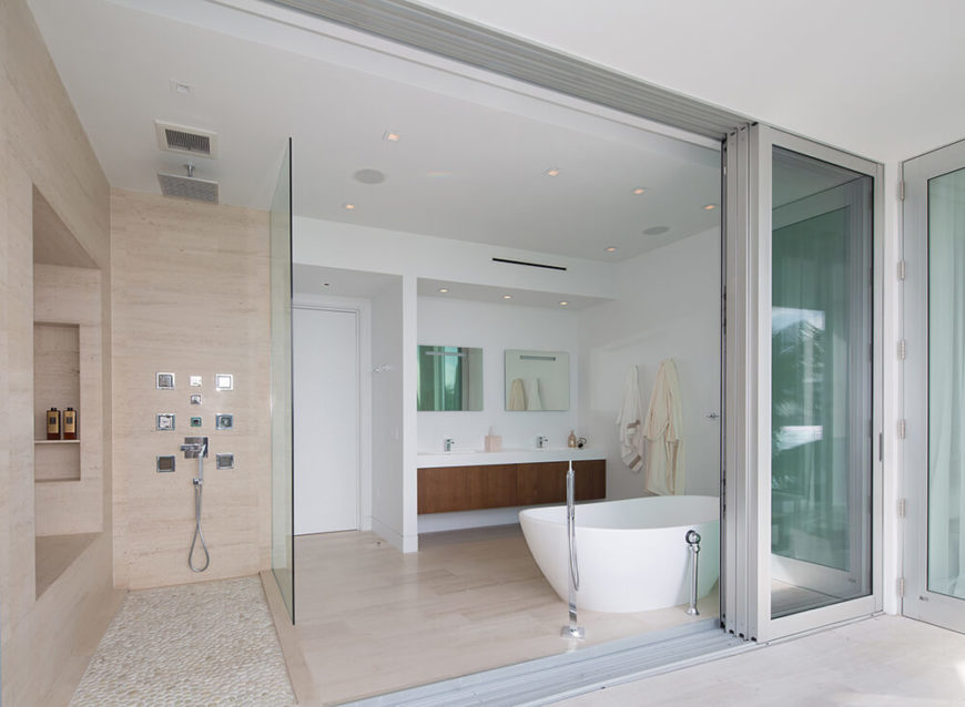 Moving upstairs to the master bathroom, we see the way glass panels are used to visually separate the shower area from the rest of the bathroom, and accordion sliding panels can be retracted to expose the bathroom to an outdoor terrace overlooking the pool and the bay.