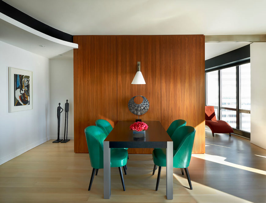 Only a few steps away from the kitchen and living room is the cozy, contemporary dining room, which is separated from the study beyond by a walnut wall that matches the kitchen cabinets. Emerald green dining chairs add a bold splash of color to the design.