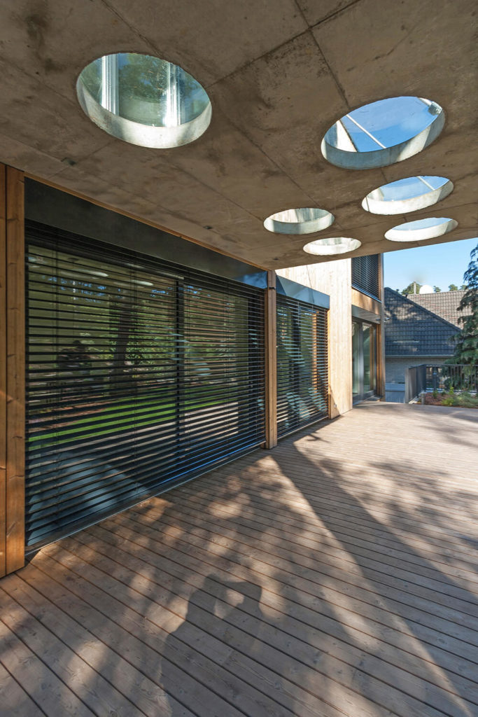 The back deck of the residence it partially covered by a concrete awning. Perfect circles have been cut out of the concrete and covered in plastic domes to allow pools of light through while protecting the residents from the elements.