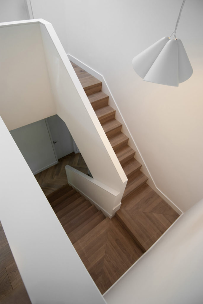 The stairway leading up to the second floor changes up the material of the floor to transition between the floors. The white walls keep the simple style while the addition of the wood floor warms up the space for the sleeping areas of the house. The simple white pendant lights brighten up the space.