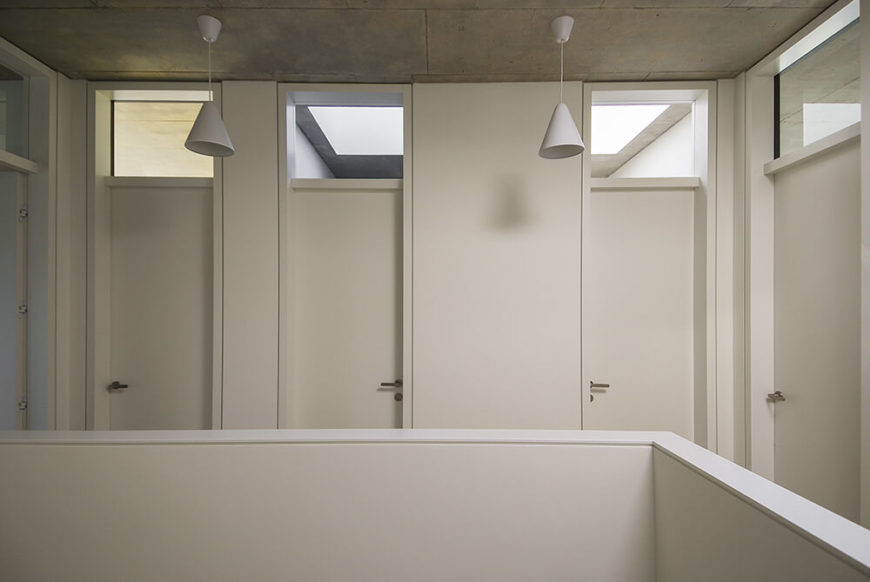 The second floor hallway is lined with simple white doors and uses the same concrete ceiling that was utilized on the first floor. Each door leaves into a different sleeping area, the main bathroom, and the laundry and storage area.