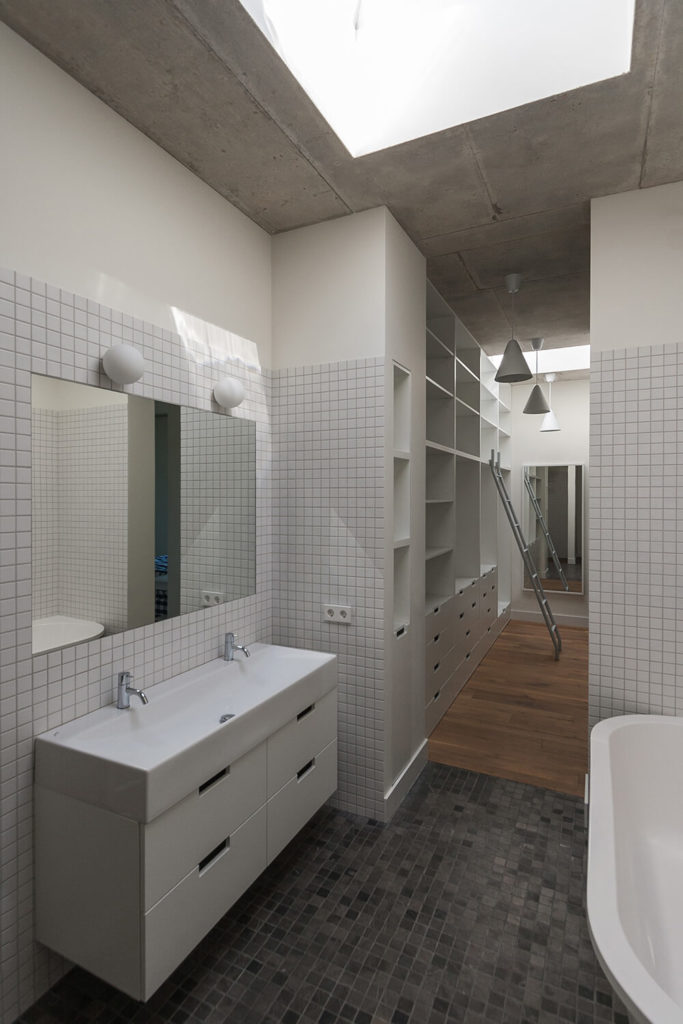 The master bathroom and walk-in closet are narrow but fully equipped with a double vanity and a soaking tub. A large skylight fully lights the room. White tiles keep the pale color palette of the rest of the house and the tiles from the first floor make another appearance in the bathroom.
