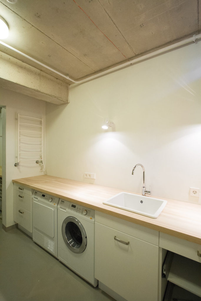 The laundry space is also on the second floor and features a long wood countertop and white cabinetry. The concrete ceiling is present in this room too.