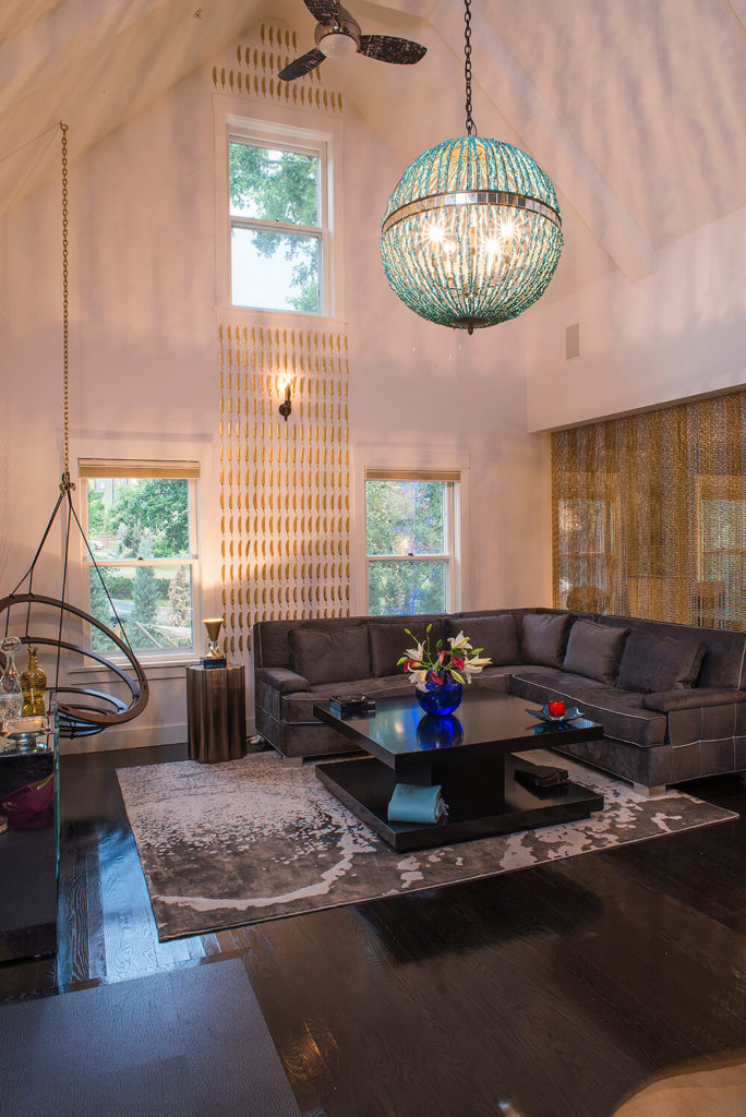 The turquoise chandelier hangs above a sleek black two-tier coffee table, surrounded by unique furniture, including a basket chair hung in the left corner. The high vaulted ceiling results in an expansive space.
