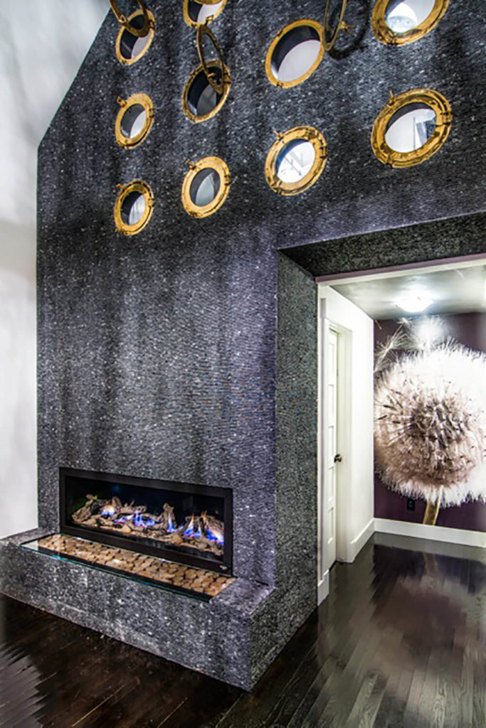 The unique fireplace, crafted from recycled Travertine tile and marble, reaches up and over the doorway, encompassing an entire feature wall. It's an anchor element, bringing a sense of gravity to the eclectic space.
