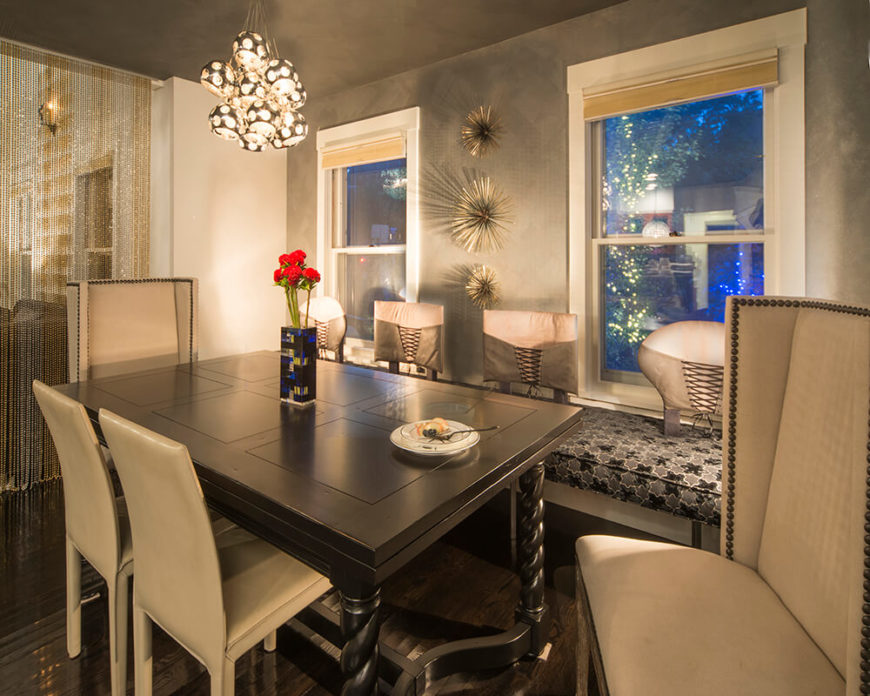 The dining room, divided from the living room by a bespoke bead wall, features a more elegant and restrained look, with a neutral palette and custom lighting solutions. The dining table in dark wood is flanked by soft beige chairs and a highly patterned bench built into the wall.