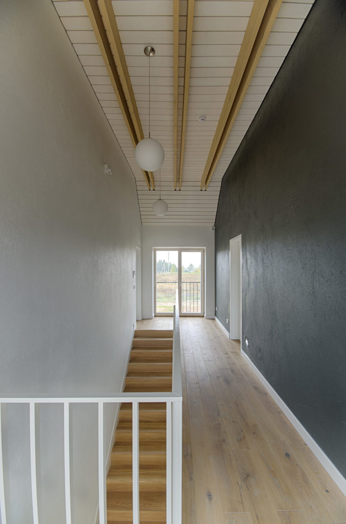 This view from atop the stair case reveals the chalky hardwood flooring and textured walls. Wood paneling similar to the exterior of the house covers the ceiling, with pendant orb lighting and golden wood rafters.