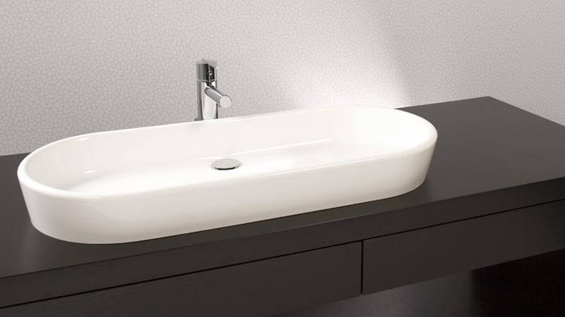 The enormously long VOV 836A sink stretches into a boat-like form, dominating a sleek, slim vanity countertop. This sink requires wall or countertop plumbing installation and is available in True High Gloss™ or matte finishes.