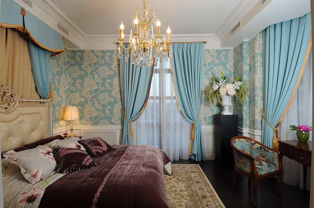 Charming master bedroom clad in lovely blue floral wallpaper and lighted by a fancy gold chandelier that hung over the cream tufted bed dressed in mauve bedding.