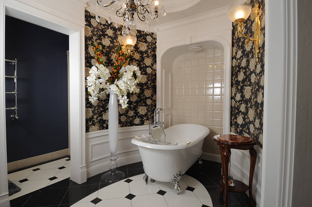 Gorgeous master bathroom clad in classy floral wallpaper offers a clawfoot bathtub situated in the tiled inset wall. It is accompanied by a tall flower vase and rich wood side table lighted by wall sconces and chandelier.