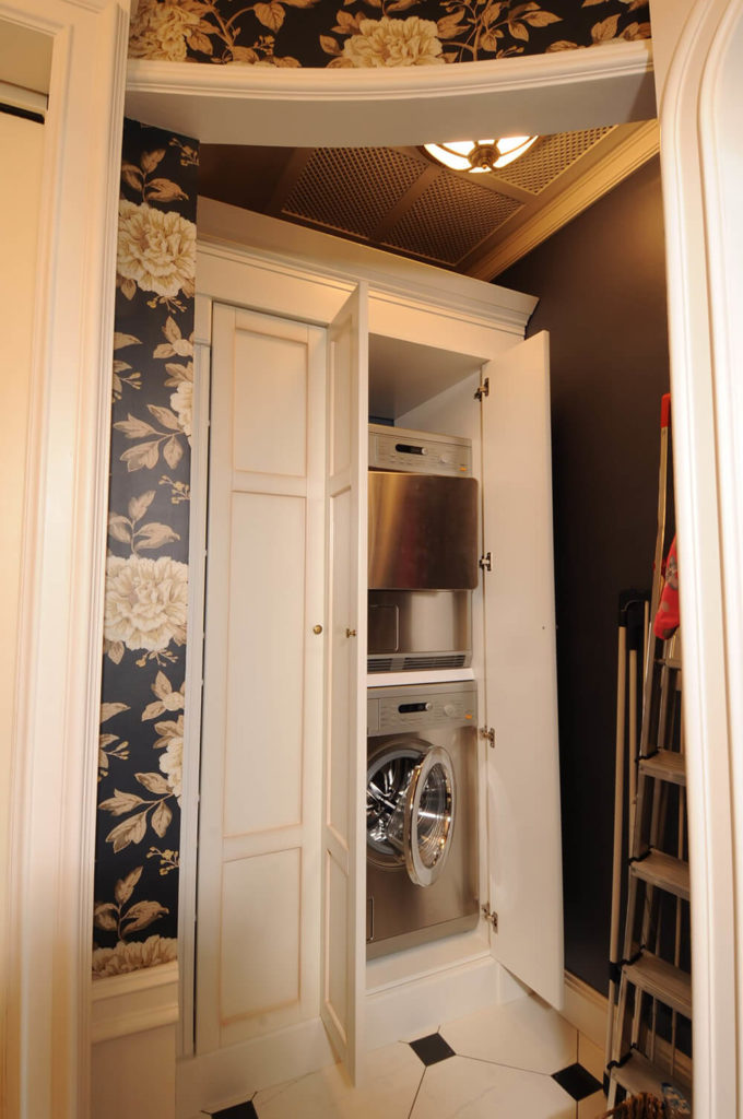 This discreet laundry space is accessed directly from the main bathroom, tucked into a well lit corner off the circular main body of the room. The functional aspects are well hidden behind ornate cabinetry.