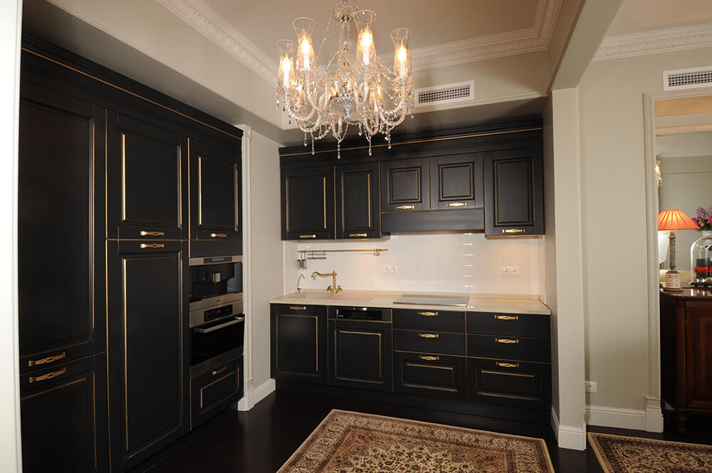 This kitchen looks so elegant with its black with gold shade cabinetry and kitchen counter lighted by a glamorous chandelier set on a lovely tray ceiling.