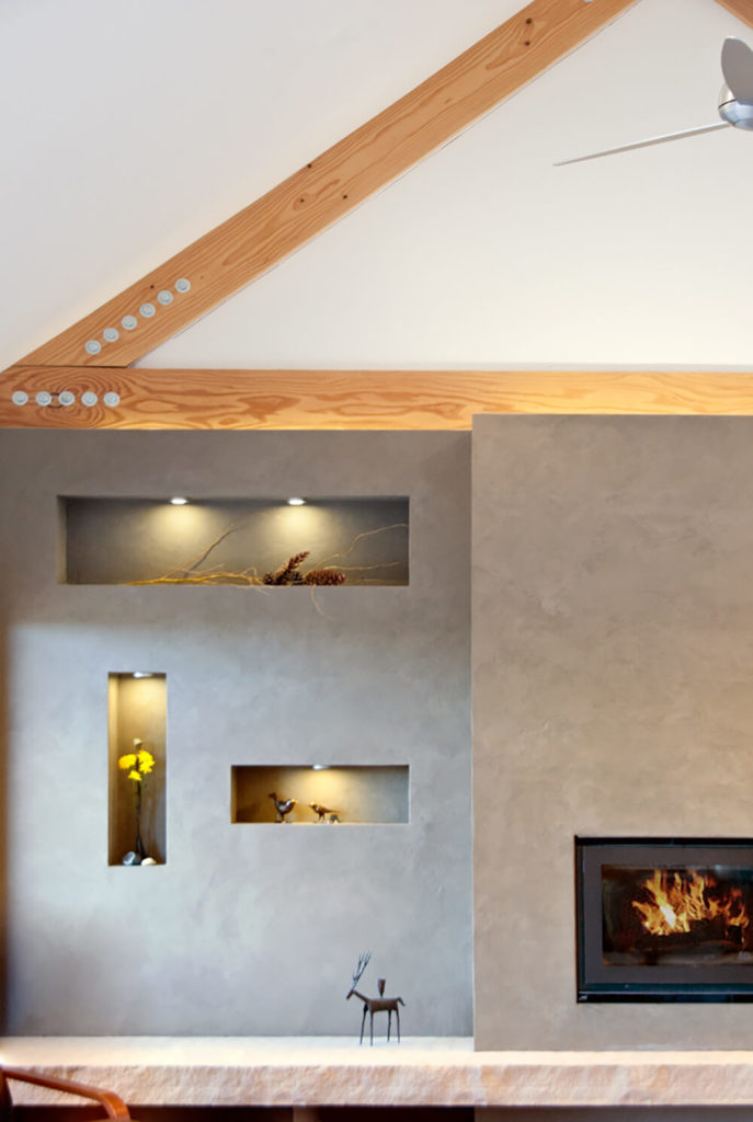 Small cutouts in the fireplace wall feature inner lighting and perfect placement for the homeowner's artwork. Subtle details like this help make the minimalist space into a welcoming retreat.