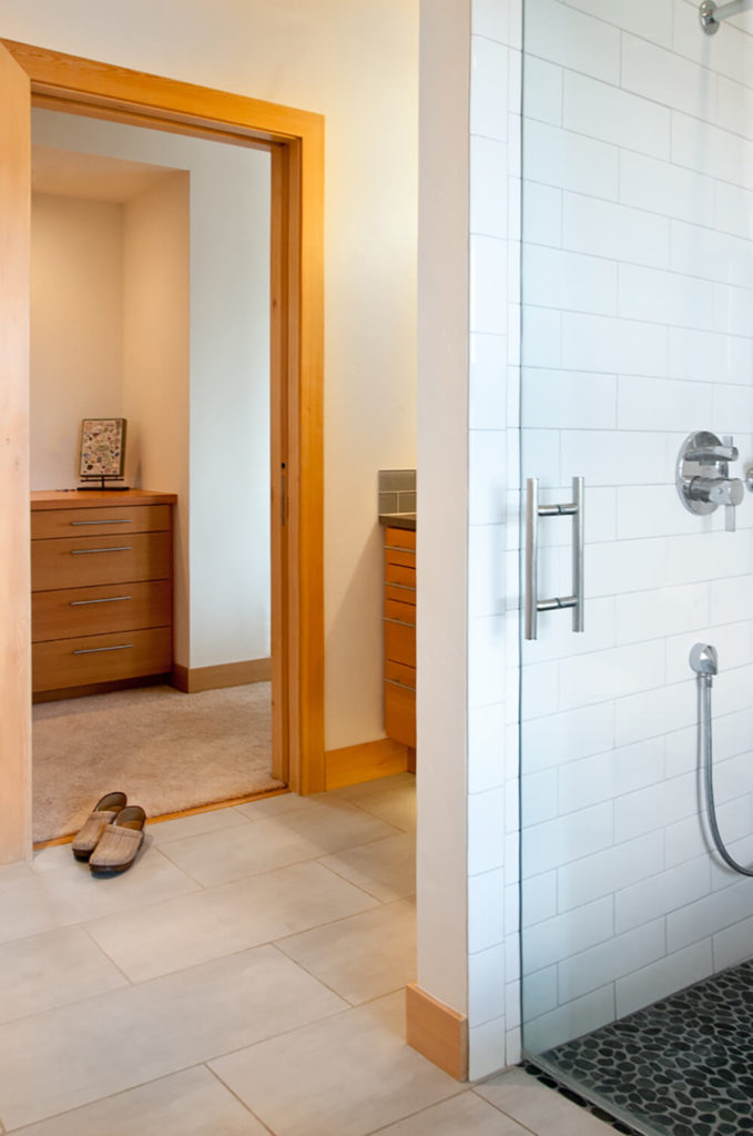 The master bath suite features a glass enclosed walk-in shower with white tile walls, a change of material while keeping the same color palette used throughout the home as stylistic connective tissue.