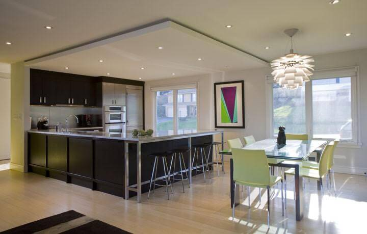 Contemporary kitchen with a shade of dark counter and cabinetry along with a dine-in table set and a breakfast bar space.