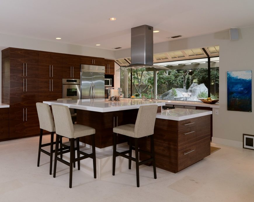 Large kitchen with white walls and wooden cabinetry along with stainless steel appliances and quartz countetops featuring a breakfast bar.