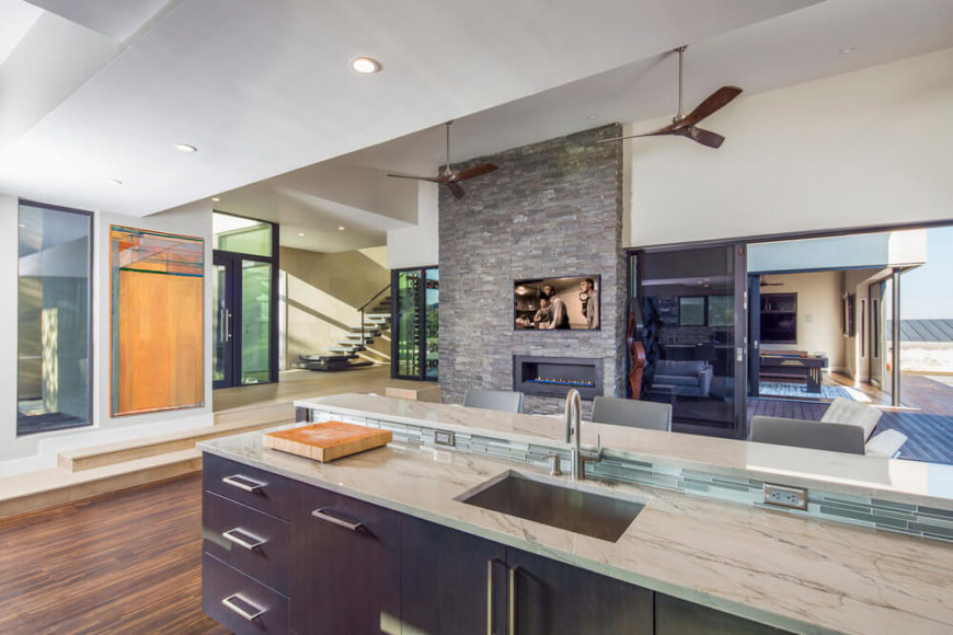 Kitchen with hardwood floors and marble countertops along with a breakfast bar lighted by recessed ceiling lights.