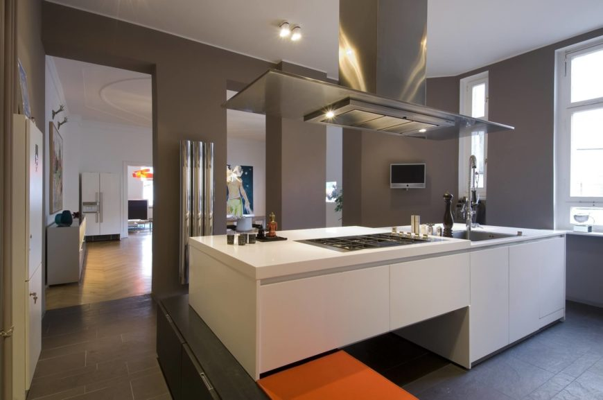 Modern kitchen with gray walls and white large center island.