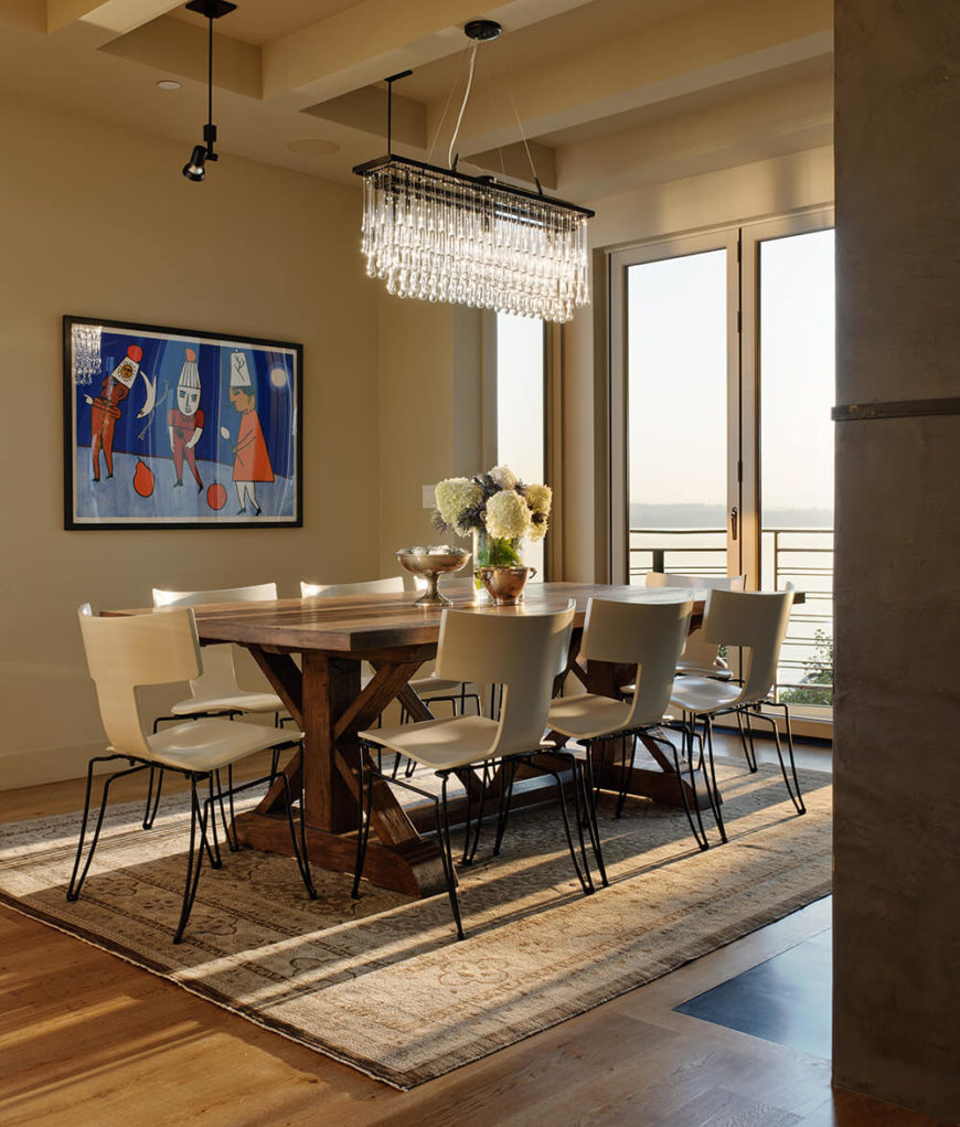 The dining room centers a large all-wood rustic styled table over a patterned area rug, surrounded by sleekly modern white chairs. Above, a rectangular chandelier hangs from one of the exposed ceiling beams.