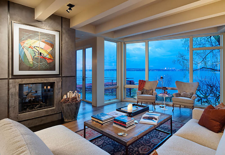The living room itself is dominated by a massive fireplace at left, accessible from both sides and wrapped in grey concrete. A bold colorful painting breaks up the neutral color palette.