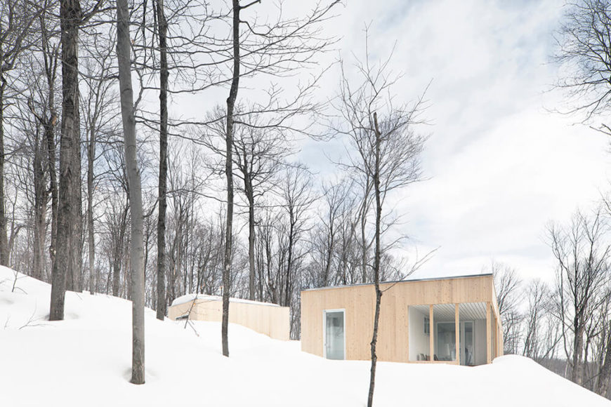 Tucked into the pristine snowy hillside, we see the light natural wood elegantly rising along with the surrounding forest. Large expanses of glass allow for a direct connection with the interior.