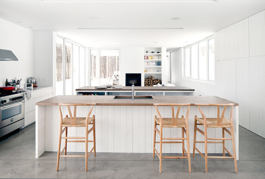 Viewed head on, we see the pair of large islands that define the kitchen within the larger open space. Natural wood countertops add contrast and another connection to nature.
