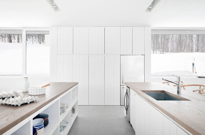 The opposite kitchen wall is a series of uniform cupboards that blend perfectly into a whole. The sleek stainless steel refrigerator is tucked into the right side, between two expanses of large windows.