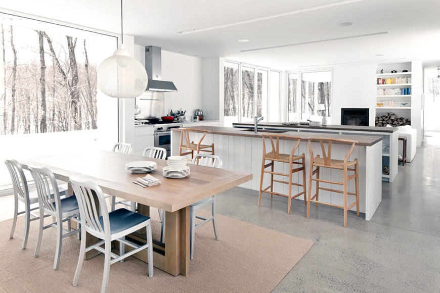 Inside, we see the vast open space at the heart of the home, combining the dining, living room, and kitchen functions. The light use of natural wood tones acts as subtle contrast in the nearly all-white interior.